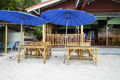 Bamboo table and chair on beach with blue parasol Stock Image