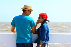 Holiday relaxing,man woman couple smiling and relax happiness st. Holiday relaxing,man women couple smiling and relax happiness stay on bridge near the beach Royalty Free Stock Images