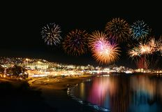 Holiday resort fireworks. Water reflecting night fireworks in seashore holiday resort festive stock photos