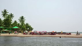 Holiday resort on water's edge. Idyllic holiday resort on sandy beach by the sea stock footage