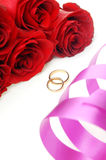 Holiday ribbon and wedding rings with flowers Stock Photos