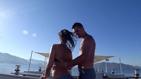 Holiday romance, cheerful dancing of pair in love into bathing suits have fun on sea jetty on background of mountains at. Summer resort stock footage