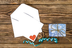 Holiday/romantic/wedding/valentine Day background with small blue handmade gift box, envelope, message card  and ribbon Stock Image