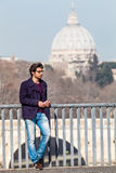 Holiday in Rome, Italy. Handsome young trendy on the bridge. A trendy handsome young boy dressed leaning on the railing of a bridge in the historic center of Stock Images