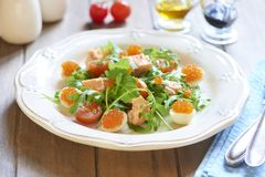 Holiday salad with salmon, quail eggs, cherry tomatoes and red caviar Royalty Free Stock Photography
