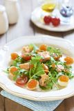 Holiday salad with salmon, quail eggs, cherry tomatoes and red caviar Stock Image