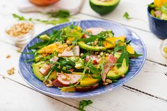 Holiday salad with smoked chicken, mango, avocado and arugula. Royalty Free Stock Photo
