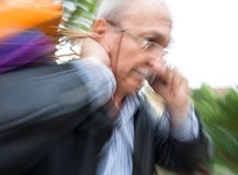 Holiday sales. An elderly man with many shopping bags in his han Royalty Free Stock Photos