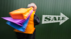 Holiday sales. An elderly man with many shopping. Bags in his hand. Intentional motion blur royalty free stock images