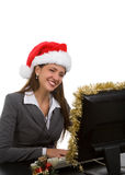 Holiday Sales Support. Young woman in santa hat and phone headpiece doing holiday sales calls Royalty Free Stock Photo