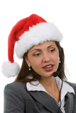 Holiday Sales Support. Young woman in santa hat and phone headpiece doing holiday sales calls Royalty Free Stock Image