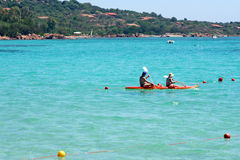 Holiday in Sardinia. 2 people canoeing in the med off the coast of Porto Istano, sardinia, in summer stock images