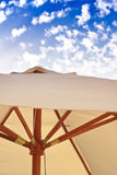 Holiday scene, beach umbrella and blue sky. A holiday-inspired shot of a beach umbrella under a bright blue sky royalty free stock photography