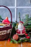 Holiday scene with cookies and Santa statue. Holiday scene with cookies in a basket  and Santa statue with evergreen branches and a window in front of a snowy Stock Photo
