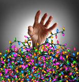 Holiday Season Stress. Concept as a human hand escaping from a chaotic tangled mess of decoration lights as a symbol of seasonal distress and social planning Royalty Free Stock Images