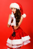 Holiday secret. Attractive young woman in Santa Claus costume over red background. Christmas Royalty Free Stock Image