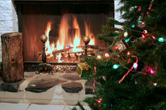 Holiday setting. Fireplace & Christmas tree during the holidays Royalty Free Stock Image