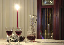 Holiday Setting with Red Wine. Holiday setting of red wine, candle, decanter with grandmother clock in background Stock Photos