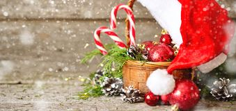 Holiday Shiny Christmas banner basket with balls, toys, candy and pine cones, santa claus hat on vintage Wooden Background Royalty Free Stock Photography