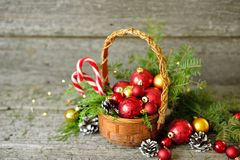 Holiday Shiny Christmas composition basket with balls, toys, candy and pine cones, santa claus hat on vintage Wooden Background Royalty Free Stock Photos