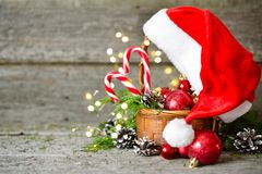 Holiday Shiny Christmas Composition basket with balls, toys, candy and pine cones, santa claus hat on vintage Wooden Background Stock Photography