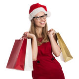 Holiday shopper. Happy woman holiday buyer wearing Santa Claus hat and red dress. Young attractive Caucasian female in eyeglasses holding holiday shopping bags Royalty Free Stock Photo