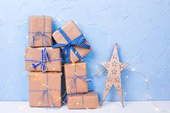 Holiday shopping concept. Decorative star and stack or pile of wrapped boxes with presents and fairy lights on white textured background against blue wall royalty free stock image
