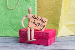 Holiday shopping concept. Wooden puppet sitting on gift box and holding card with inscription holiday shopping. Consumerism, sale and retail royalty free stock photography