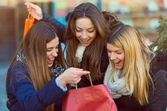 Holiday shopping girls in the street with bags. Group of girls in the street in the winter time shopping together stock photography