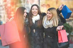 Holiday shopping girls in the street with bags. Group of girls in the street in the winter time shopping together royalty free stock photo