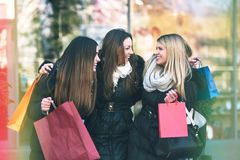 Holiday shopping girls in the street with bags. Group of girls in the street in the winter time shopping together stock photo