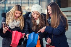 Holiday shopping girls in the street with bags. Group of girls in the street in the winter time shopping together royalty free stock photos