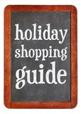 Holiday shopping guide. White chalk text on a vintage slate blackboard royalty free stock photos
