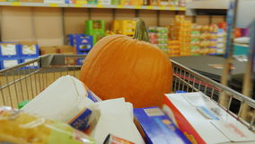 Holiday shopping for Halloween. Trolley with shopping bags and a large pumpkin goes to supermarket stock video footage