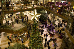 Holiday shopping mall. A shopping mall with Christmas decorations filled with customers on black Friday night Royalty Free Stock Images
