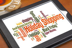Holiday shopping word cloud. On a digital tablet with a cup of tea and cookie stock photo