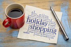 Holiday shopping word cloud. Handwriting on a napkin with a cup of coffee royalty free stock image