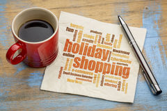Holiday shopping word cloud on napkin. Holiday shopping word cloud on a napkin with a cup of coffee stock photos