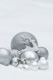 Holiday silver decorative Christmas baubles and star with Santa Claus's reindeer at natural snow background Royalty Free Stock Photography