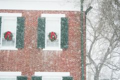 A holiday snow scene of a Christmas decorated home. A very snowy view of holiday decorated brick home Stock Photos