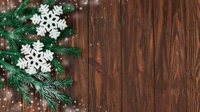 Holiday snowflakes and snow with branches of Christmas trees. On a wooden background texture for the new year Stock Photo