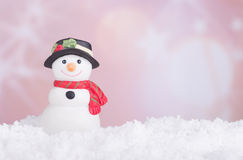Holiday Snowman Figurine. On snow with colorful background Royalty Free Stock Image