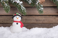 Holiday Snowman Figurine. On snow with evergreen banches and wood background Stock Image