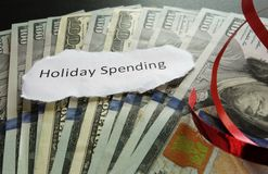 Holiday spending concept. Holiday Spending note on cash, with red ribbon Stock Photo