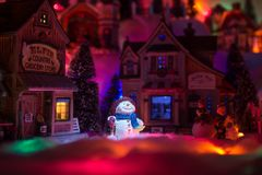 Holiday spirits of a snowman in Christmas times. Christmas lands. Lights from above shines on happy face of snowman who stands in the middle of a miniature royalty free stock images