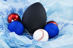 Holiday Sports Fanatic. Festive holiday ribbon, Christmas ornaments, and a football and baseball on blue tissue paper; holiday and sports items combine for a Stock Image