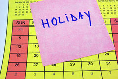Holiday sticky note on calendar. Holiday post-it on a yellow calendar Royalty Free Stock Photography