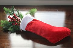 Red Christmas stocking filled with pine and berries in the sunlight. Holiday stocking filled with pine branch and berries on wood table with sunlight through a stock image