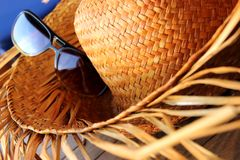Holiday. Straw hat with sunglasses on a sunny day Stock Image
