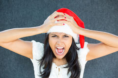 Holiday stress. Closeup portrait of a cute Christmas woman with a red Santa Claus hat, white dress, hands on head, stressed out, yelling, showing frustration Royalty Free Stock Photography